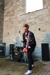 Sweden, Ostergotland, Alvastra, Teenage boy (16-17) playing electric guitarの写真素材 [FYI02203453]