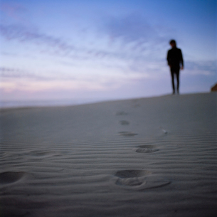 USA, Oregon, Newport, Silhouette of man standing on sandy beach at sunsetの写真素材 [FYI02203477]