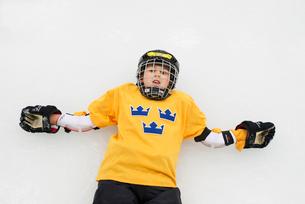 Sweden, Young male hockey player (8-9) lying on iceの写真素材 [FYI02203513]