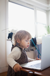 Sweden, Girl (2-3) looking at laptopの写真素材 [FYI02203538]