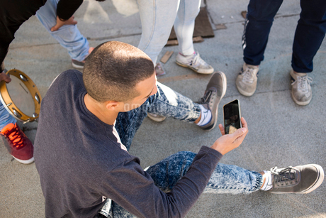 Israel, Tel Aviv, Man sitting on pavement and using mobile phoneの写真素材 [FYI02203542]
