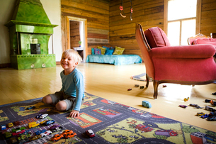Finland, Boy (4-5) kneeling on multi colored carpet in roomの写真素材 [FYI02203587]