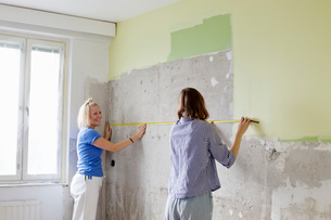 Finland, Young women measuring wall for renovationの写真素材 [FYI02203619]