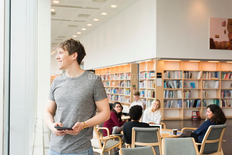 Sweden, Man standing and looking through window in libraryの写真素材 [FYI02203630]