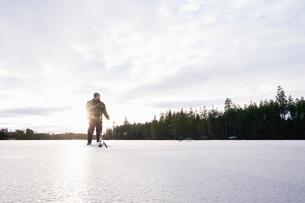 Sweden, Vastmanland, Bergslagen, Hallefors, Natsjon, Man preparing for ice fishing on frozen lakeの写真素材 [FYI02203661]