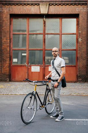Germany, Berlin, Man standing by bicycleの写真素材 [FYI02203670]