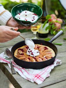 Sweden, Woman pouring cream on apple cakeの写真素材 [FYI02203676]