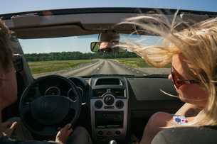 Sweden, Uppland, Couple in car driving along country roadの写真素材 [FYI02203684]