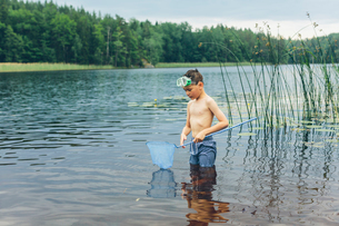 Sweden, Smaland, Mortfors, Kappemalagol, Boy (8-9-) wading and fishingの写真素材 [FYI02203697]