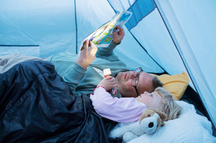 Sweden, Father and daughter (4-5) reading comic book in tentの写真素材 [FYI02203698]