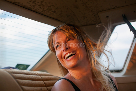 Sweden, Blonde woman laughing on back seat of carの写真素材 [FYI02203704]