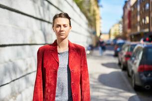 Sweden, Uppland, Stockholm, Kungsholmen, Woman in red jacket looking at cameraの写真素材 [FYI02203713]