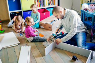 Finland, Father building cabinet for daughters (12-17 months, 2-3) in nurseryの写真素材 [FYI02203739]