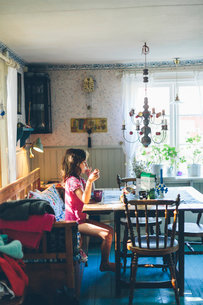 Sweden, Girl (8-9) sitting at table and eatingの写真素材 [FYI02203744]