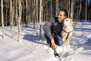 Sweden, Vasterbotten, Umea, Man kneeling with dog in snowの写真素材 [FYI02203768]