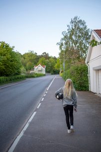 Sweden, Vastergotland, Lerum, Girl (12-13) walking with soccer ball on roadsideの写真素材 [FYI02203785]
