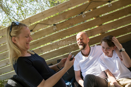 Sweden, Parents with son (14-15) laughingの写真素材 [FYI02203797]