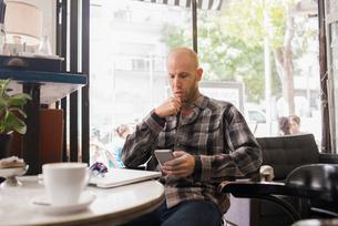 Israel, Tel Aviv, Man sitting in cafe and using phoneの写真素材 [FYI02203814]