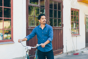 Sweden, Smaland, Mortfors, Man pushing bicycle by houseの写真素材 [FYI02203828]