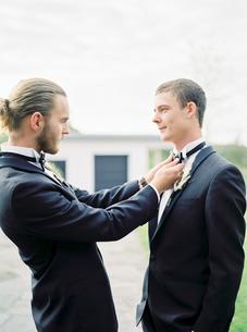 Sweden, Groom adjusting partner´s bow tie at gay weddingの写真素材 [FYI02203837]