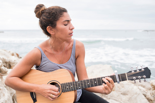 Israel, Tel Aviv, Woman playing guitar by seaの写真素材 [FYI02203867]
