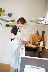 Sweden, Boy (14-15) cooking in kitchenの写真素材 [FYI02203881]