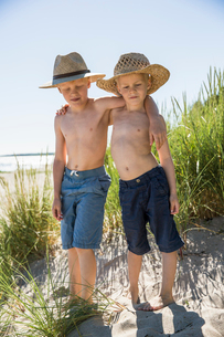 Sweden, Gotland, Shirtless boys (6-7, 8-9) in straw hats standing on sand dune at seashoreの写真素材 [FYI02203897]