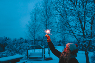 Finland, Jyvaskyla, Saakoski, Smiling woman holding sparkler in backyard at duskの写真素材 [FYI02203921]