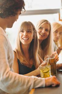 Sweden, Man talking with women in barの写真素材 [FYI02203926]