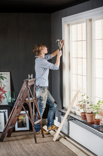 Sweden, Mid-adult woman hammering nail in living roomの写真素材 [FYI02203928]