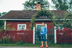 Sweden, Smaland, Mortfors, Farbo, Boy (8-9) standing in front of red houseの写真素材 [FYI02203936]