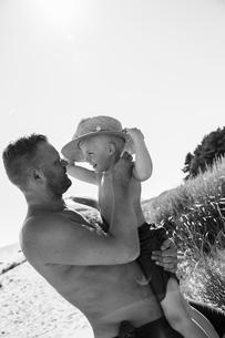 Sweden, Gotland, Shirtless man holding boy (6-7) in straw hat at beachの写真素材 [FYI02203951]