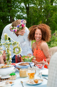 Man with flower wreath talking to girl sitting at picnic tableの写真素材 [FYI02203973]