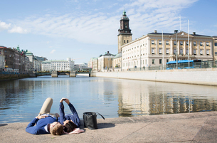 Sweden, Vastergotland, Gothenburg, Young couple lying on promenade and taking selfieの写真素材 [FYI02203981]