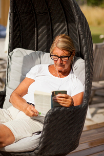 Sweden, Senior woman reading book in hooded beach chairの写真素材 [FYI02203989]