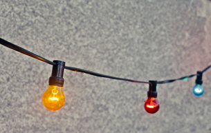 Sweden, Multi colored light bulbs hanging against wallの写真素材 [FYI02203990]