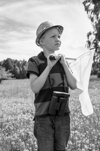 Sweden, Gotland, Boy (8-9) with butterfly net standing in meadowの写真素材 [FYI02204017]