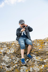 Sweden, Gotland, Boy (8-9) sitting at edge of cliff and using telephoneの写真素材 [FYI02204021]