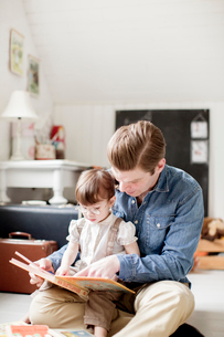 Sweden, Father reading with daughter (2-3) picture bookの写真素材 [FYI02204034]