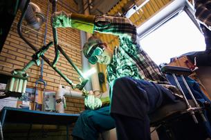 Sweden, Young man welding metalの写真素材 [FYI02204056]