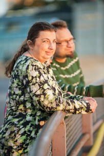 Sweden, Sodermanland, Stockholm, Sodermalm, Slussen, Friends leaning against railing at sunsetの写真素材 [FYI02204076]