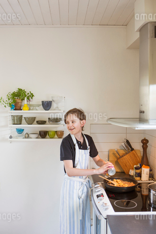 Sweden, Boy (14-15) cooking in kitchenの写真素材 [FYI02204077]