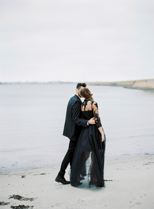 Sweden, Halland, Varberg, Young formally dressed couple walking along beachの写真素材 [FYI02204083]
