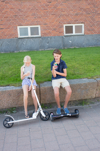Sweden, Smaland, Anderstorp, Girl (12-13) with scooter and boy (14-15) with hoverboard sitting on waの写真素材 [FYI02204091]