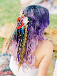 Sweden, Bride with flowers and feathers in purple hair at hippie weddingの写真素材 [FYI02204118]