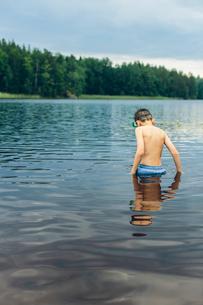 Sweden, Smaland, Mortfors, Kappemalagol, Boy (8-9-) wading in lakeの写真素材 [FYI02204125]