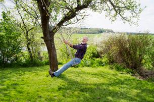 Sweden, Vastergotland, Senior man sitting on rope swingの写真素材 [FYI02204130]