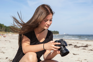 Sweden, Skane, Ahus, Teenage girl (16-17) taking pictures on beachの写真素材 [FYI02204160]