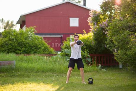 Sweden, Norrland, Vasterbotten, Mature man exercising with weights in backyardの写真素材 [FYI02204168]
