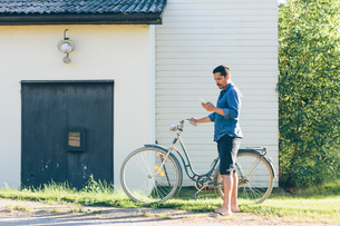 Sweden, Smaland, Mortfors, Man standing by house with bicycle and using phoneの写真素材 [FYI02204170]